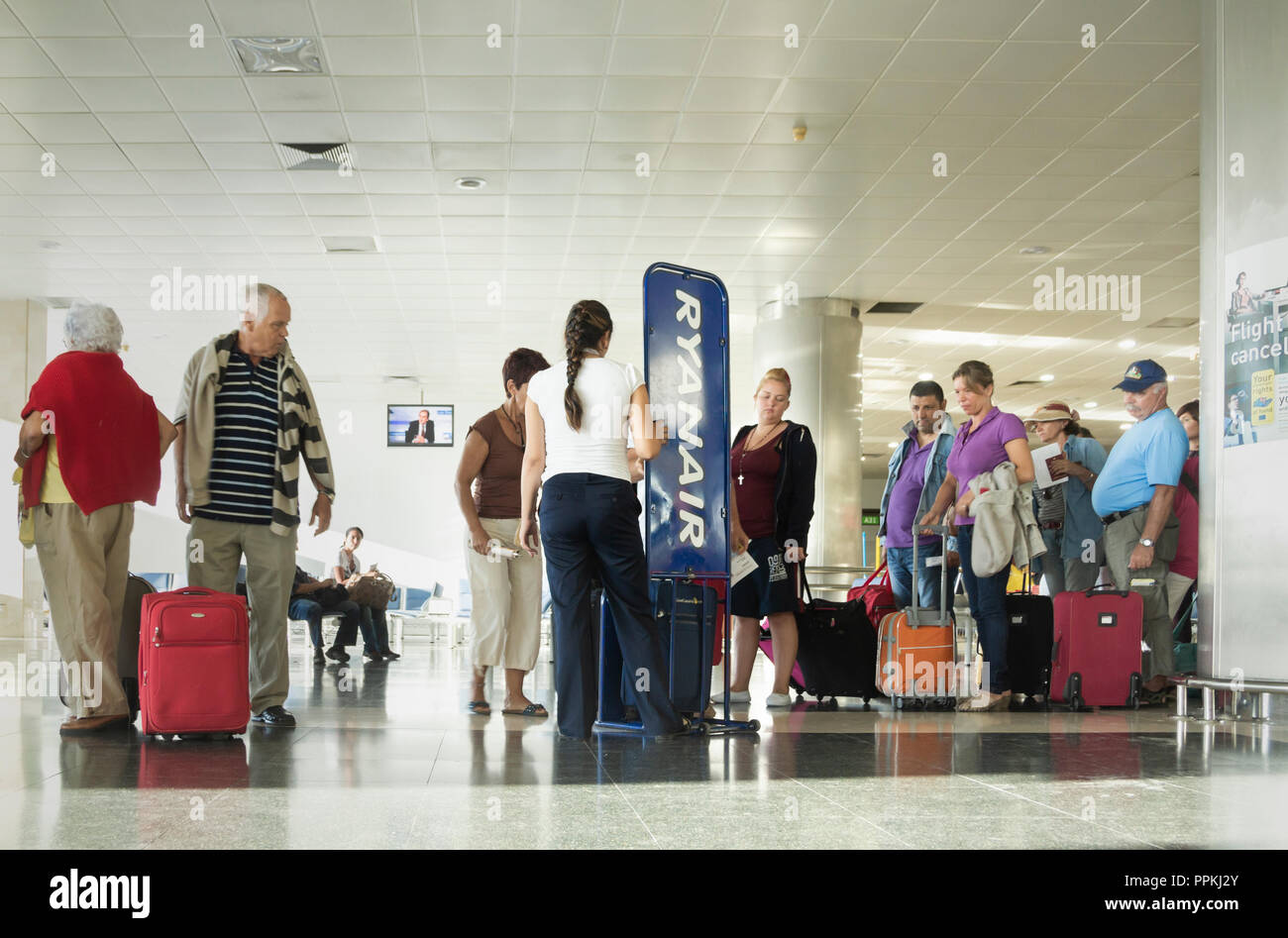 Ryanair worker checking hand luggage size prior to boarding. - Stock Image