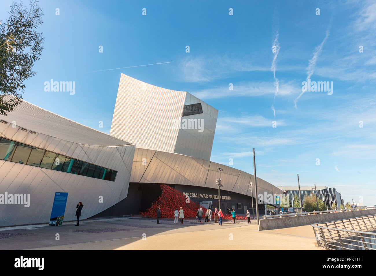 Imperial War Museum North with the iconic red poppy sculpture Wave by artist Paul Cummins and designer Tom Piper outside. - Stock Image