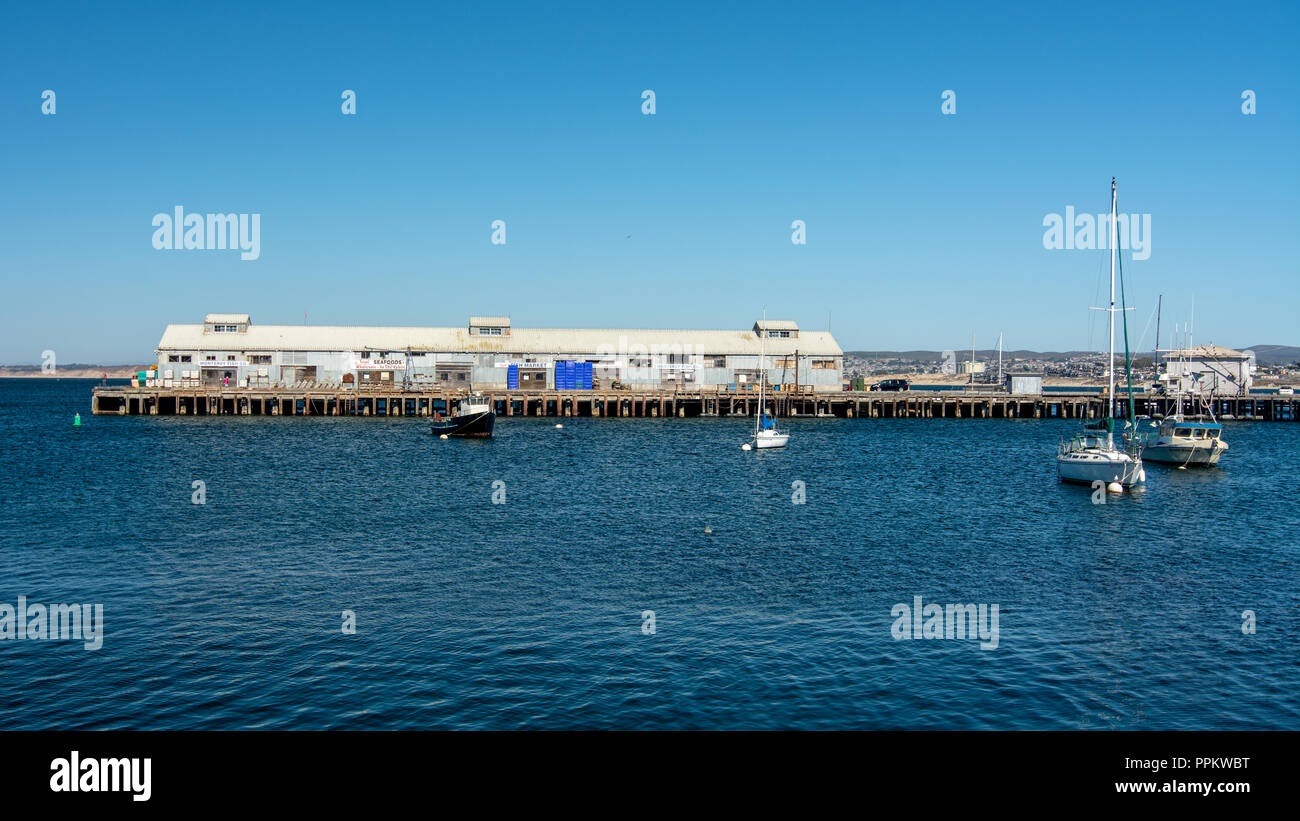 Monterey, CA, USA, 15 September  2018.  Monterey pier 1, a commercial pier, viewed from from pier 2 , mainly touristic, on a blue  cloudless sky day i - Stock Image