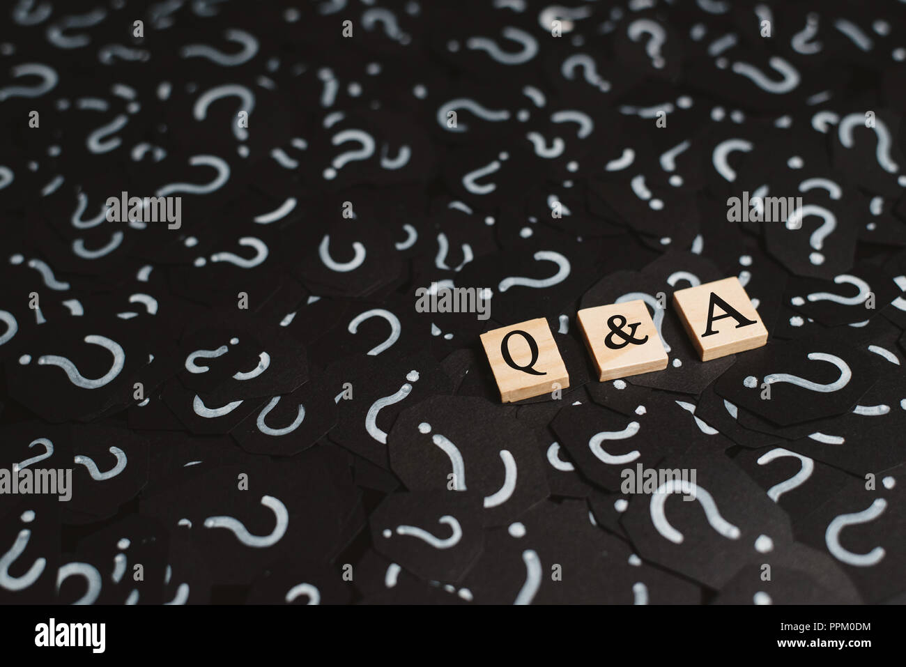 wooden alphabet tiles with Q&A letter on black paper with QUESTION MARK. Concept of Question and Answer Q&A online assist - Stock Image