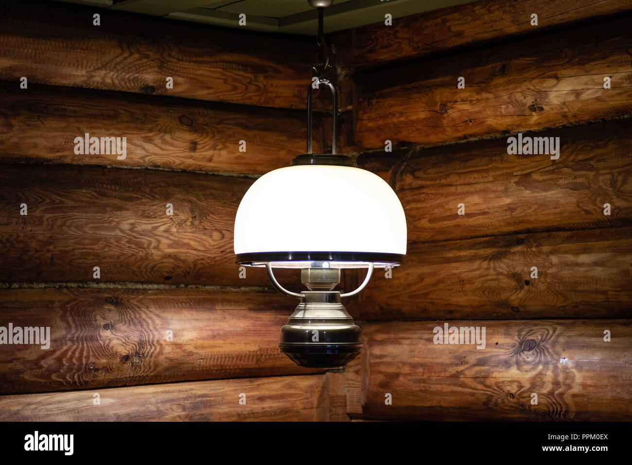 Interior of the log house with an electric lamp. - Stock Image