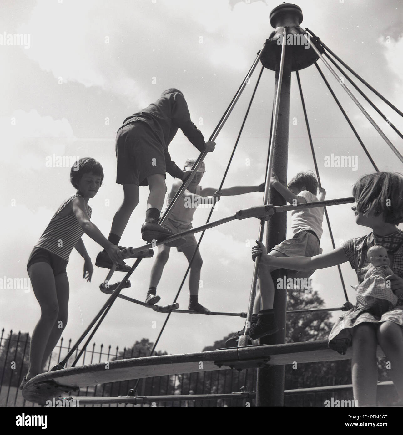 1960s, historical, young chidlren outside at a playground hanging onto the crossbars on an exciting metal swing or merry-go-round ride, known as the 'witches hat', England, UK. In the later decade, they were removed from playgrounds due to health and safety concerns about children falling off them. - Stock Image