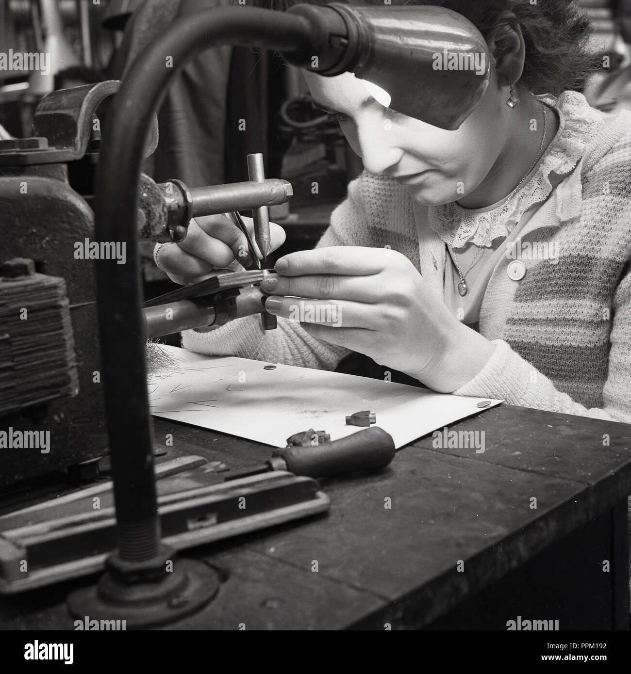 1950s, historical, a woman doing intricate, close-up work at a wooden bench with a machine tool at the Ever Ready Company, a leading British manufacturer of batteries, torches, bicycle lamps and radios in this era. With a number of factories around Britain and thousands of workers, Ever Ready dominated the zinc-carbon battery market both in the UK and in South Africa. - Stock Image