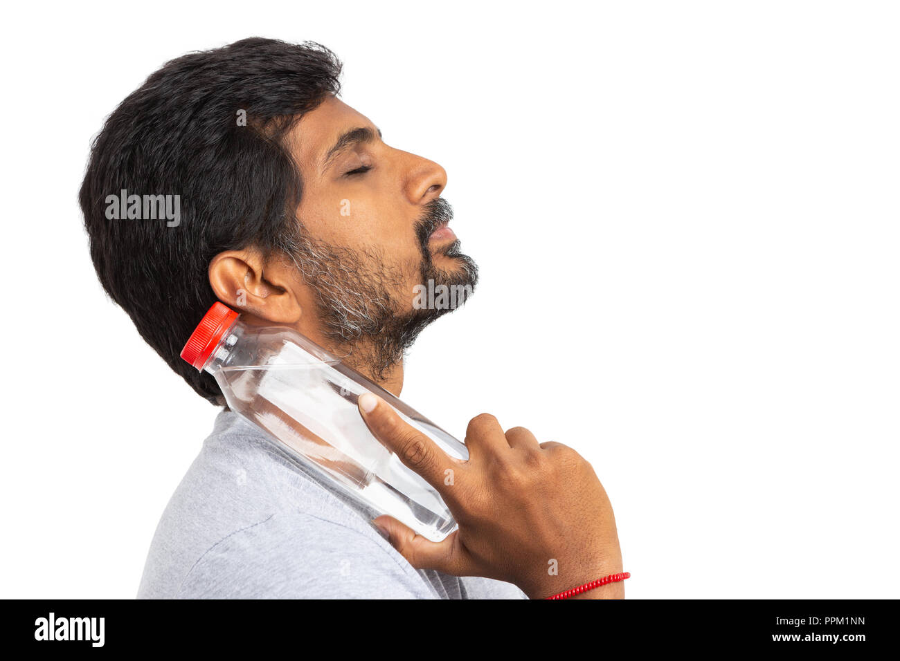 Indian person cooling down neck by touching it with a cold water bottle isolated on white background as summer refreshment concept - Stock Image