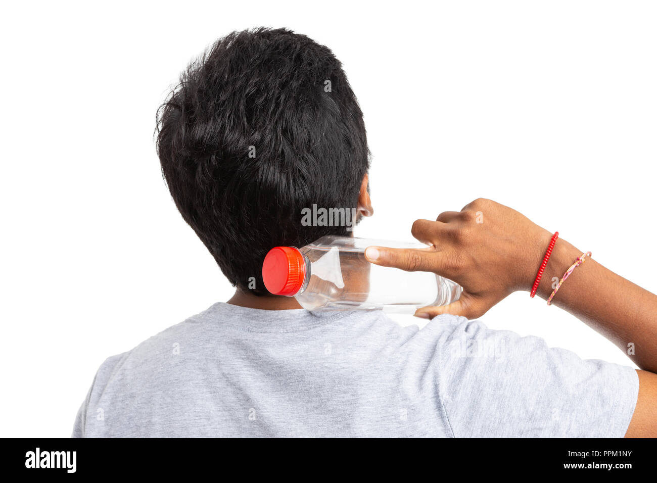 Man from India touching neck with plastic water bottle with the back to the camera isolated on white background as stay hydrated concept - Stock Image