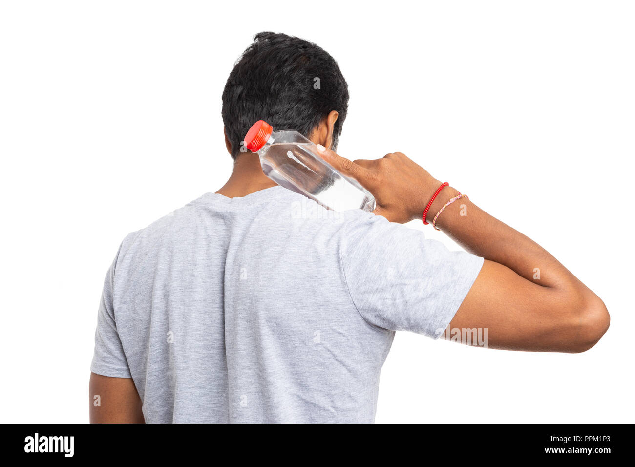 Indian person touching back of neck with plastic water bottle not looking at camera isolated on white as stay hydrated concept - Stock Image