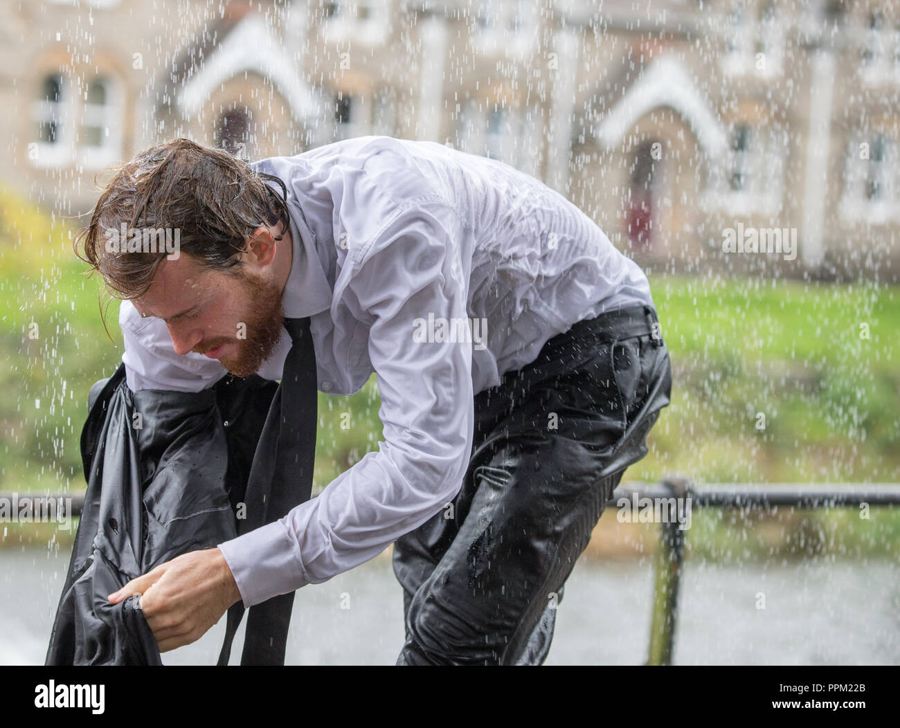 A man in a suit caught in a very heavy rain shower - Stock Image