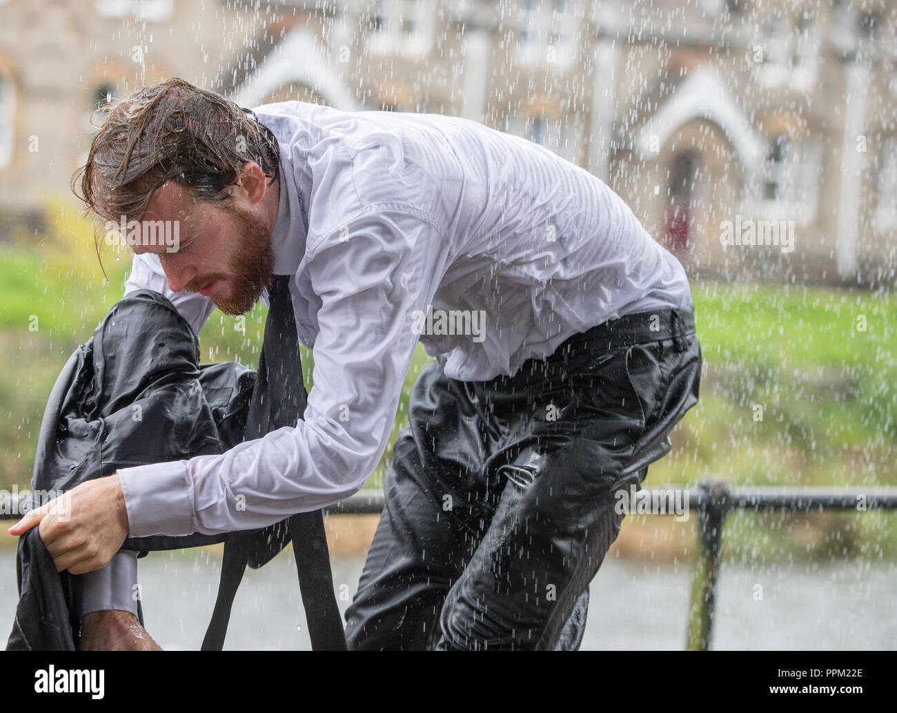 A man in a suit caught in a very heavy rain shower Stock Photo