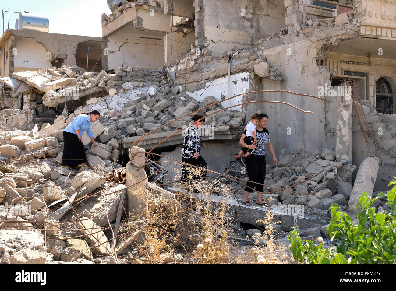 Family members in the rubble of a house destroyed by bombing in the war against ISIS in Bashiqua, northern Iraq, Kurdistan - Stock Image