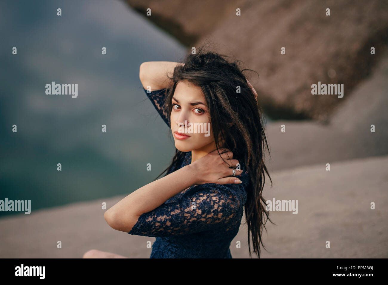 Lifestyle portrait of a woman brunettes in background of lake sitting in sand on a cloudy day. Romantic, gentle, mystical, pensive image of a girl. Gi - Stock Image