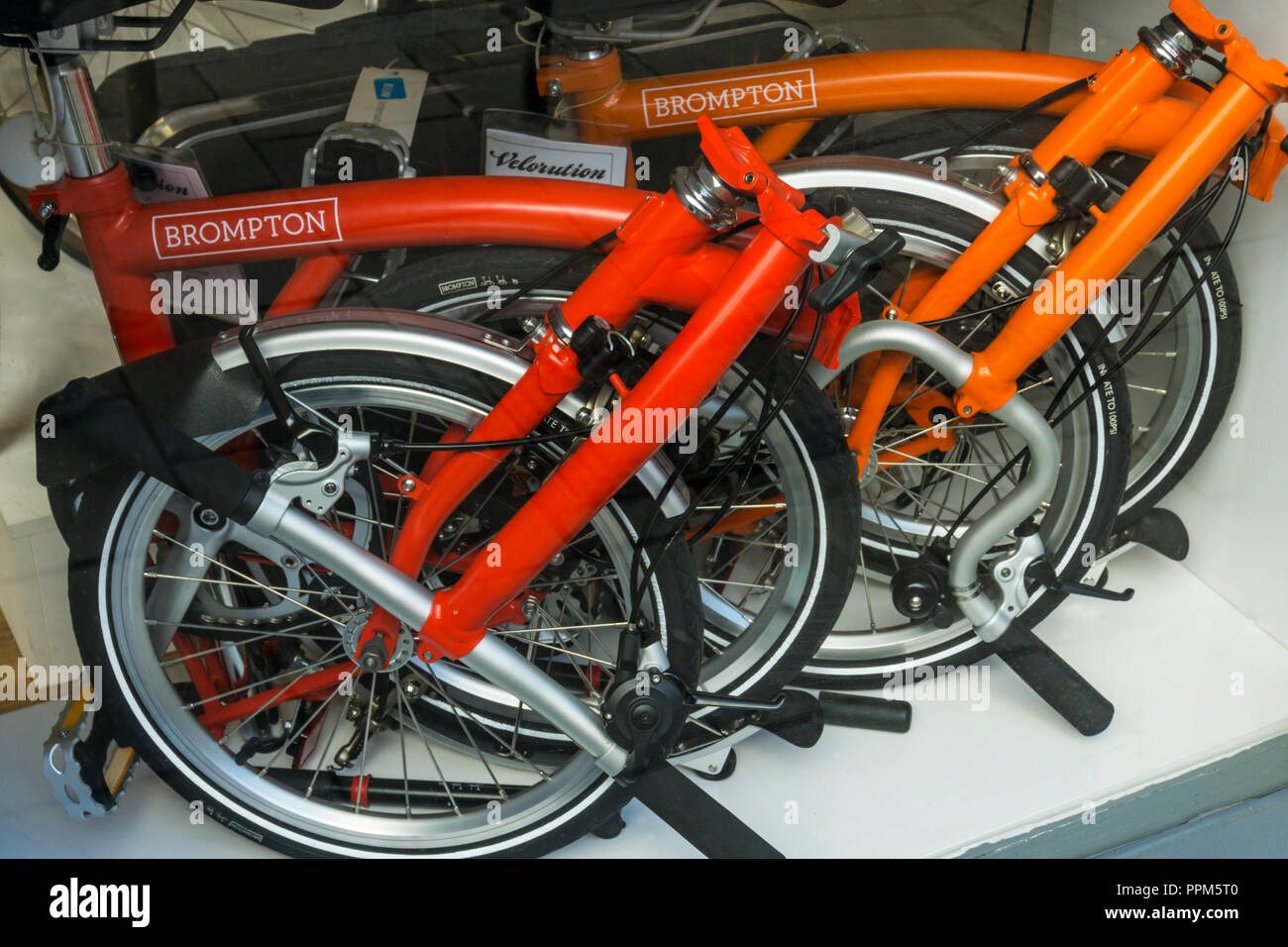Brompton folding bicycles folded into a small space in a shop window. - Stock Image