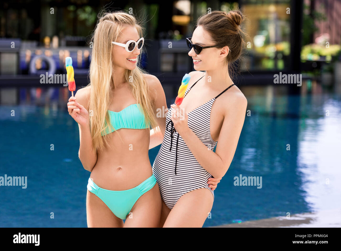 happy young embracing women in swimsuit and bikini with popsicles at poolside Stock Photo