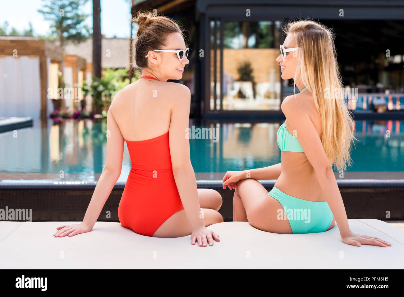 rear view of attractive young women relaxing on sun lounger at poolside and looking at each other - Stock Image