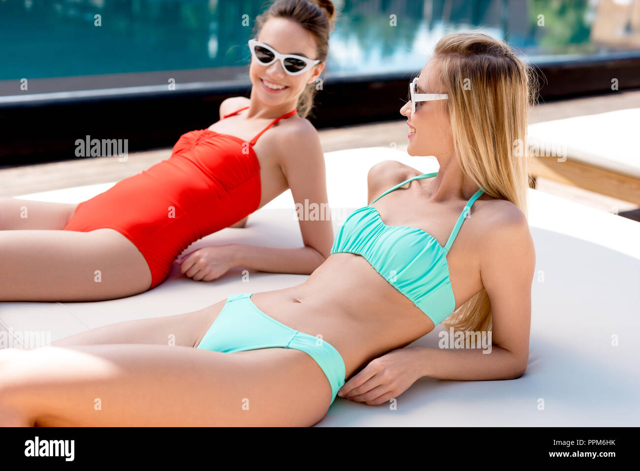 smiling young women relaxing on sun lounger at poolside and looking at each other - Stock Image