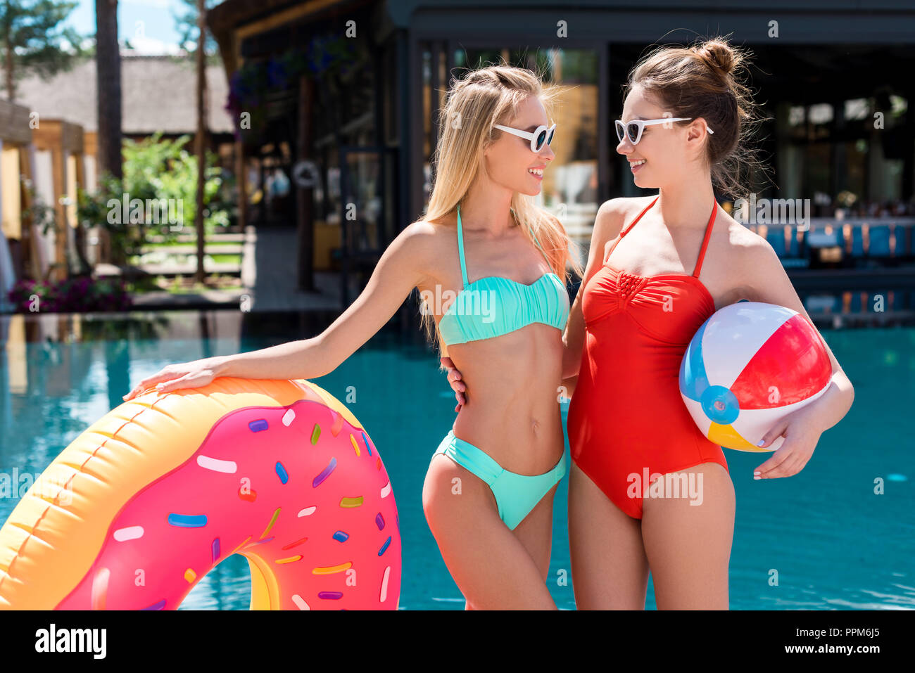 beautiful young women with inflatable ring in shape of donut and beach ball standing at poolside and looking at each other - Stock Image