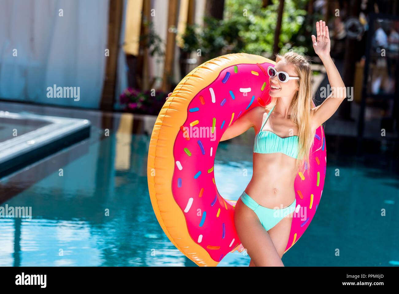 beautiful young woman inflatable ring in shape of donut greeting someone at poolside - Stock Image