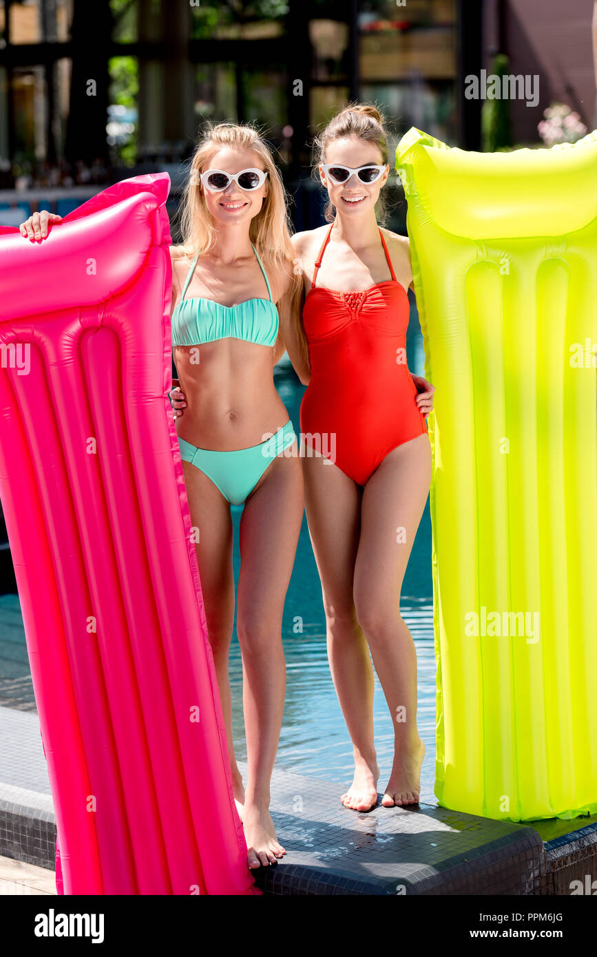 attractive young women with inflatable mattresses standing at poolside and looking at camera - Stock Image
