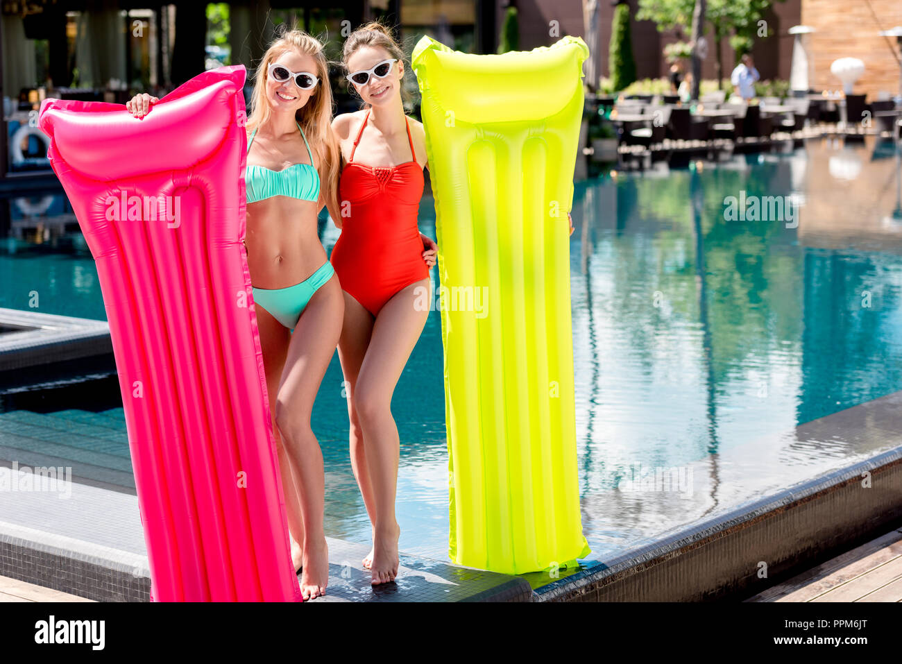 beautiful young women with inflatable mattresses standing at poolside and looking at camera - Stock Image