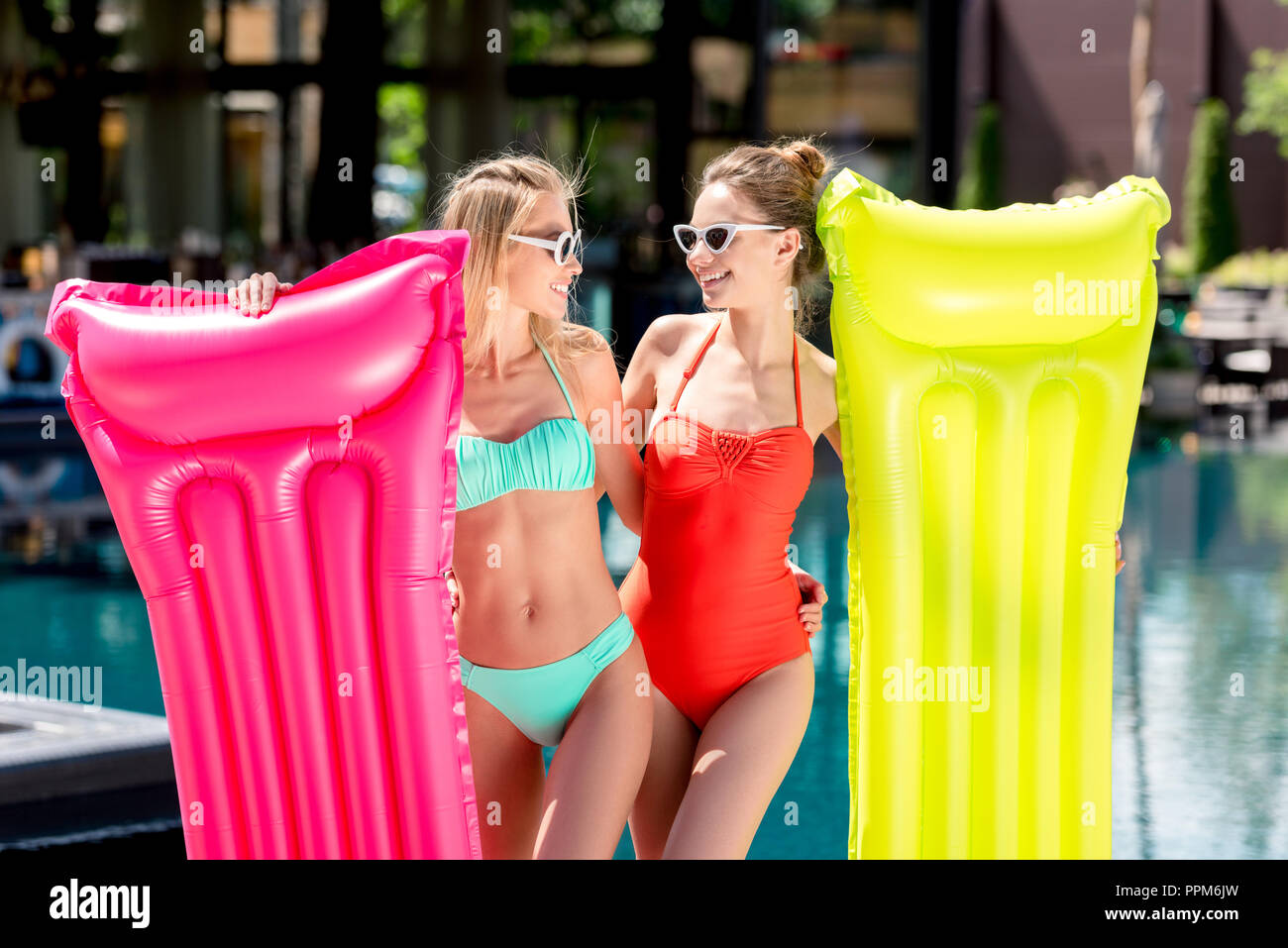 beautiful young women with inflatable mattresses standing at poolside and looking at each other - Stock Image