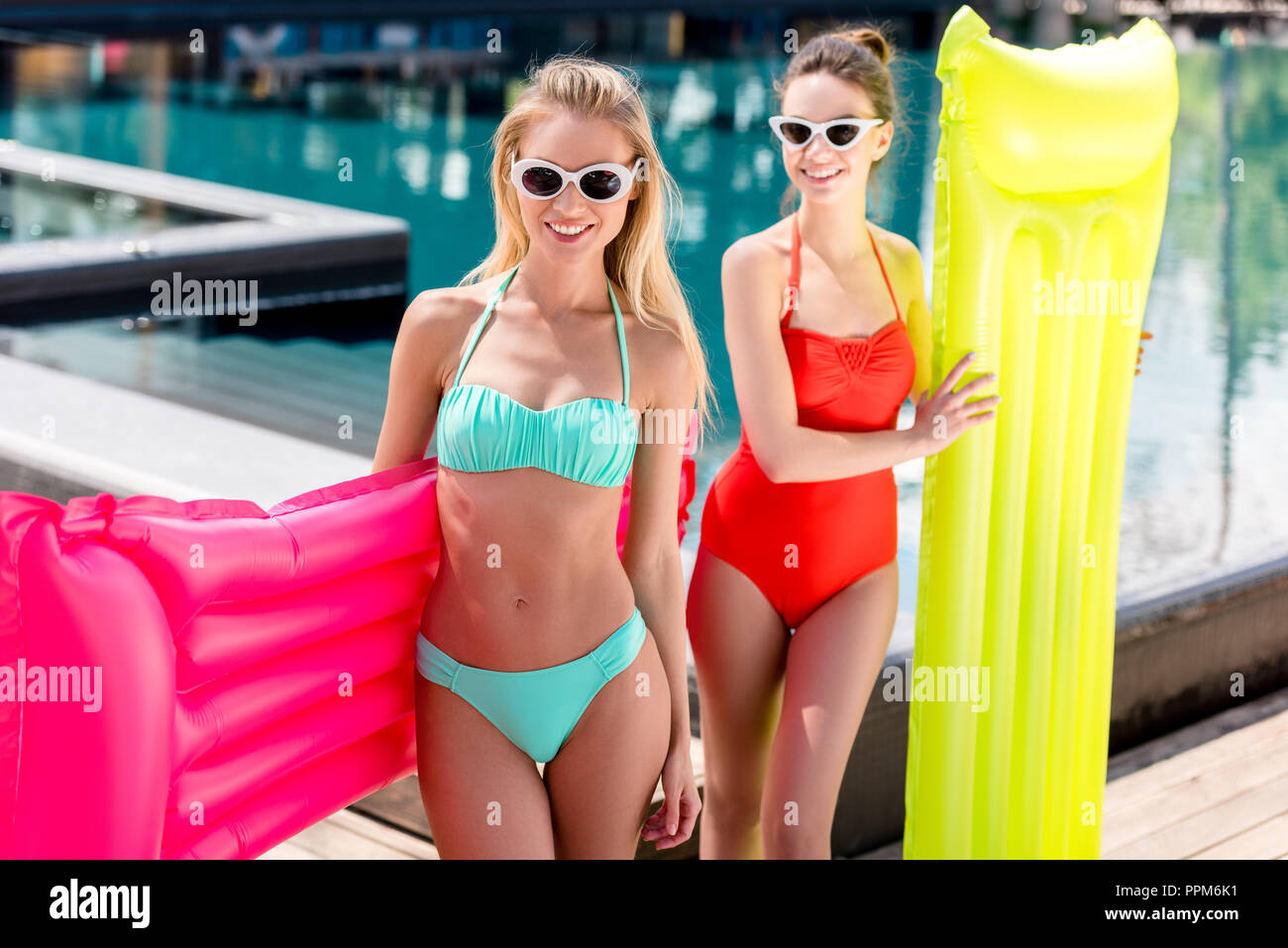 happy young women with inflatable mattresses standing at poolside - Stock Image