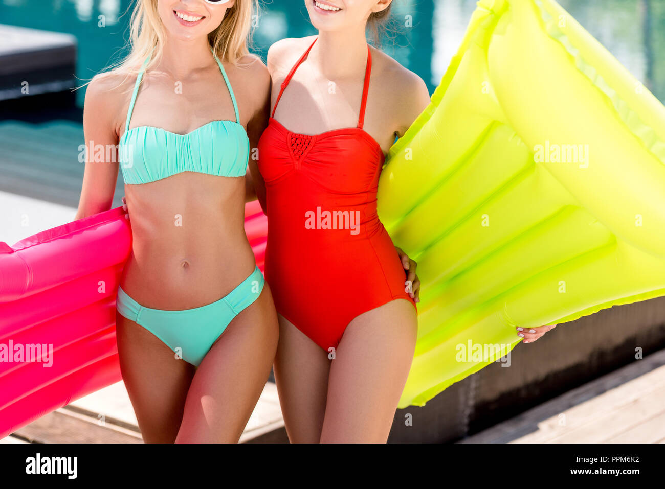cropped shot of smiling young women with inflatable mattresses standing at poolside - Stock Image