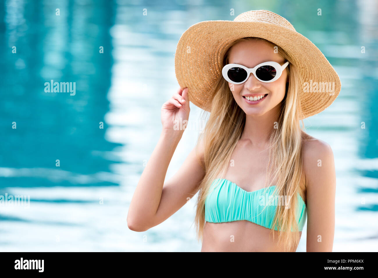 beautiful young woman in straw hat with vintage sunglasses and bikini at poolside - Stock Image