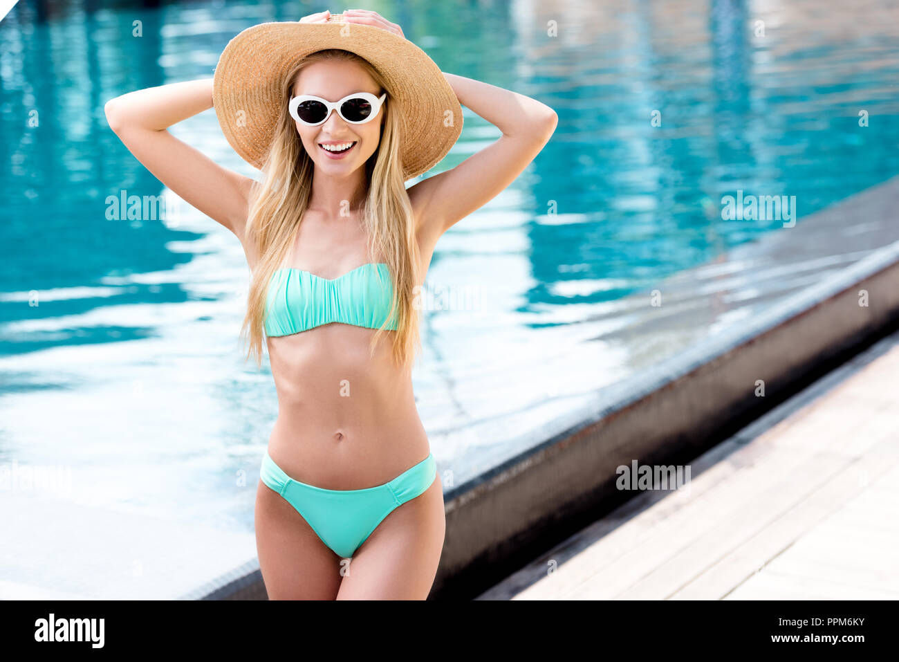 happy young woman in straw hat with vintage sunglasses and bikini at poolside - Stock Image