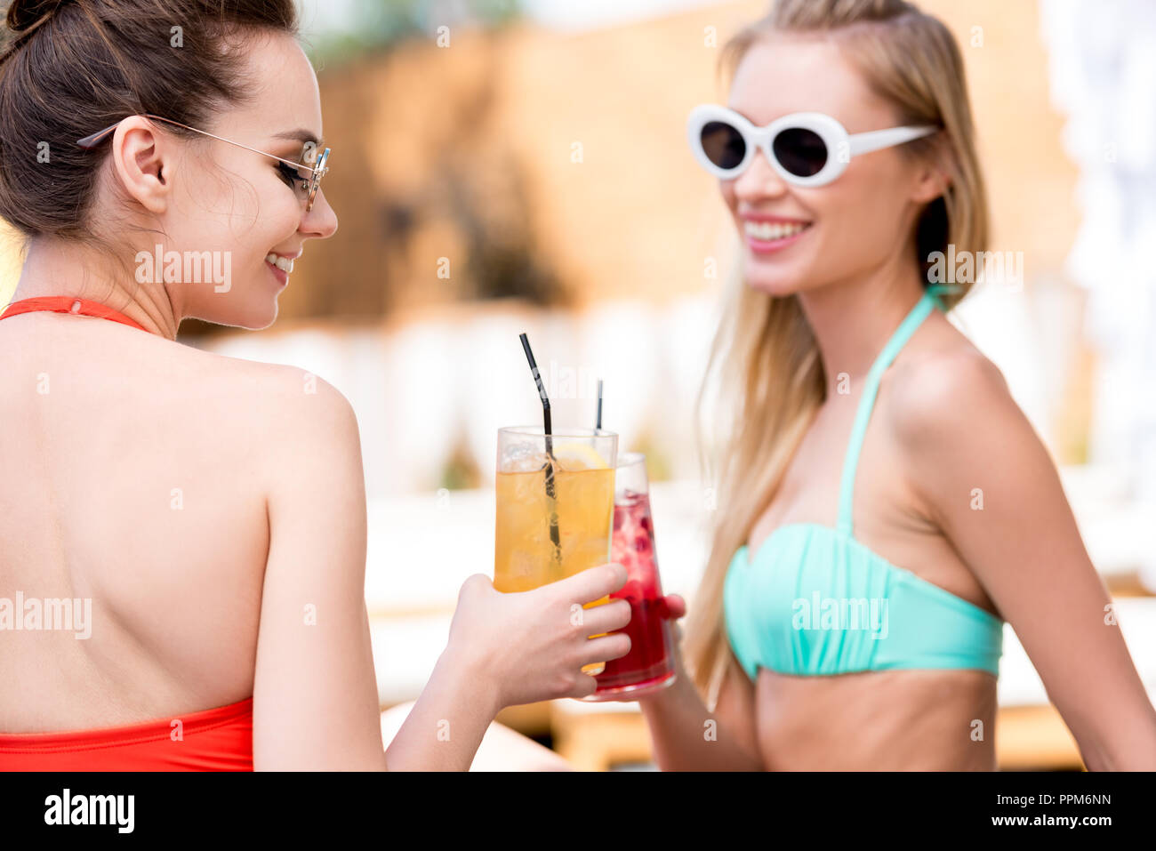 happy young women clinking glasses of cocktails at poolside - Stock Image