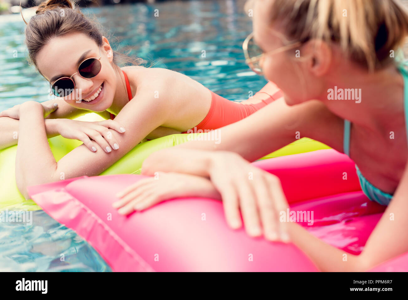 attractive young women lying on inflatable mattresses in swimming pool - Stock Image