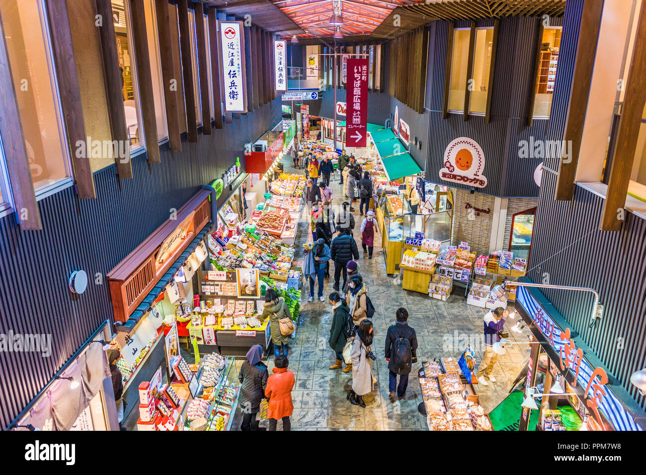 KANAZAWA, JAPAN - JANUARY 20, 2017: Early morning shoppers peruse fresh seafood at the the Omicho Market. - Stock Image