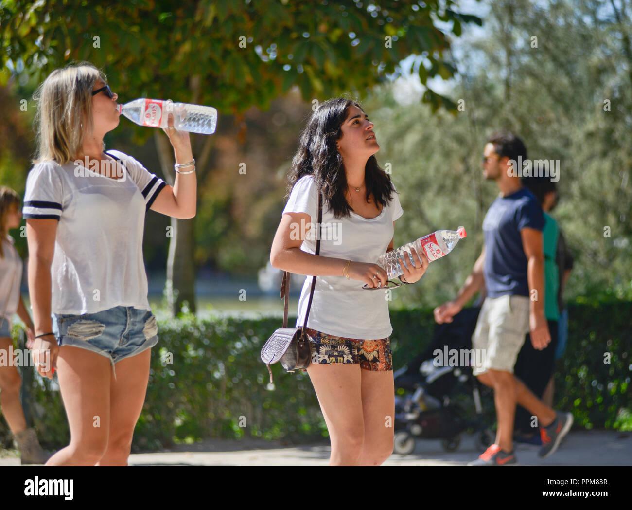 Tourists drinking water during summer. Buen Retiro Park - Parque del Buen Retiro, Madrid, Spain - Stock Image