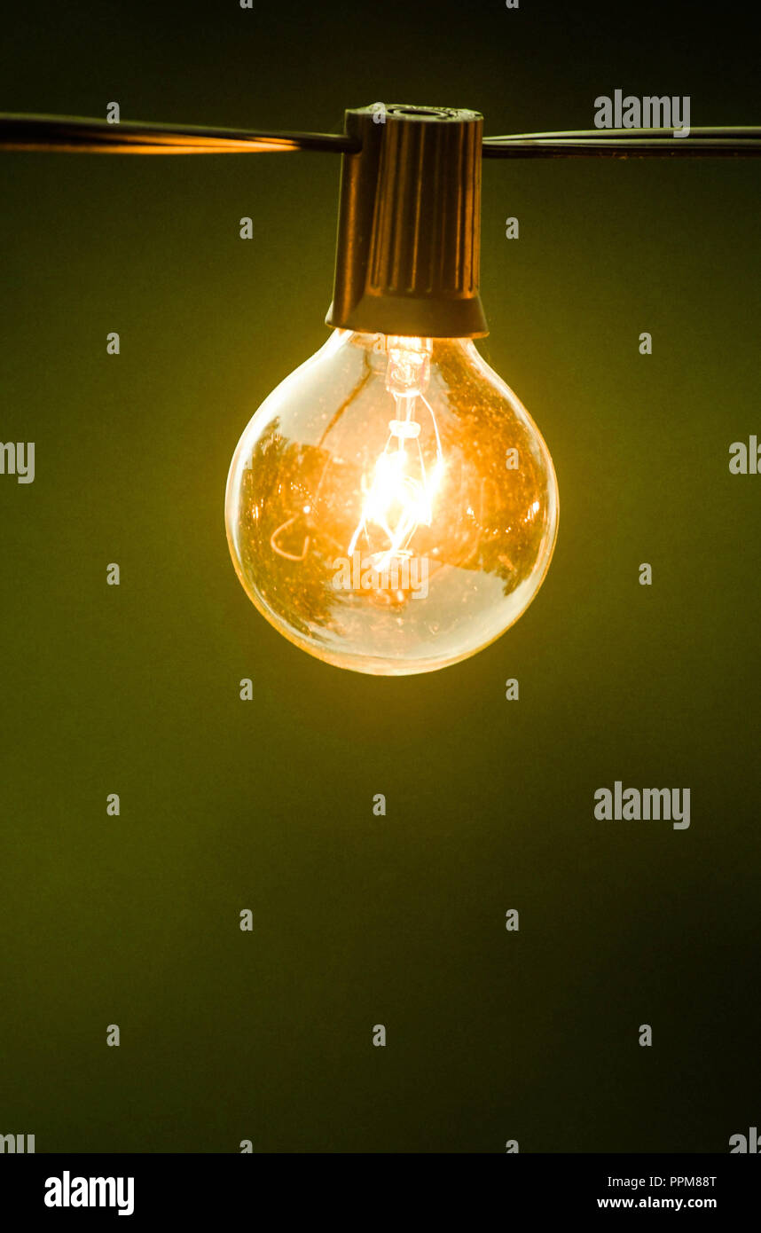 An outdoor lightbulb, glowing yellow, hanging on a black cord in early evening Stock Photo