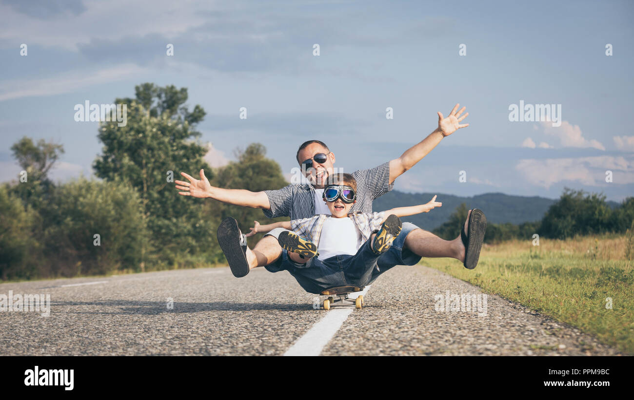 Father and son playing on the road at the day time. People having fun outdoors. Concept of friendly family. - Stock Image