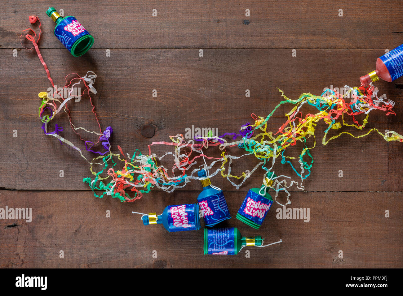 Exploded party poppers with their paper streamers on the floor. - Stock Image