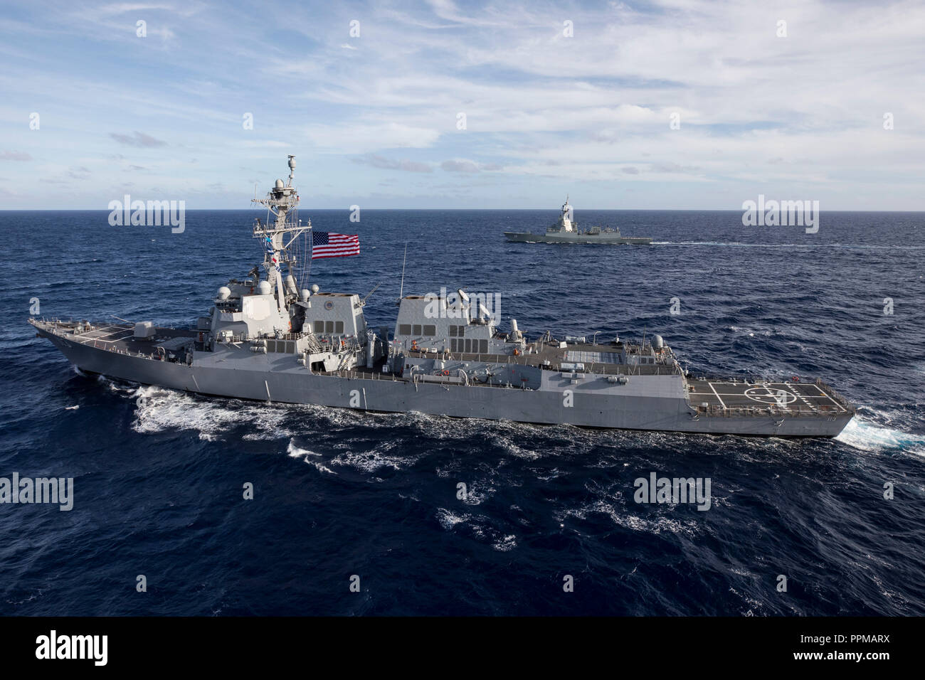 """The U.S. Navy ship USS John Finn (DDG 113) and the Royal Australian Navy ship HMAS Hobart (DDG 39), both guided missile destroyers, conduct naval formations off the coast of Oahu, Hawaii, Sept. 21, 2018. The two ships cooperated in a variety of ship maneuvers part of the """"Mateship"""" festivities to commemorate the 100 year anniversary since the two nations fought side by side in 1918 during World War I. (U.S. Marine Corps photo by Sgt. Jesus Sepulveda Torres) - Stock Image"""