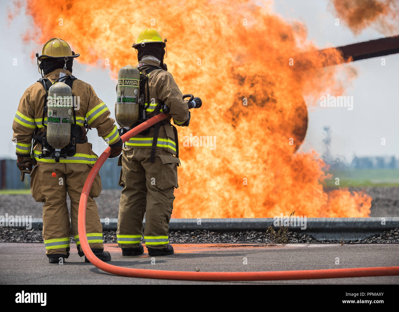 Yokota Air Base and Marine Corps Air Station Iwakuni firefighters prepare to battle a fire during a joint fire training, at YAB, July 17, 2018. During the two day live fire training, Air Force and Marines got an opportunity to enhance firefighting skills during simulated aircraft and structural burns and flash over scenarios. (U.S. Air Force photo by Airman 1st Class Gabrielle Spalding) - Stock Image