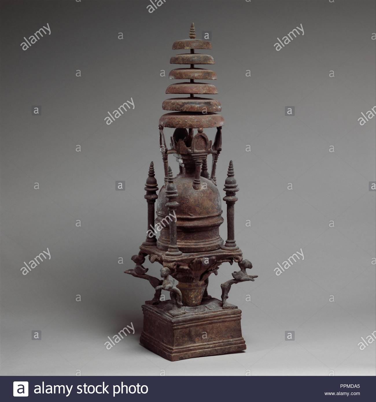 Reliquary in the Shape of a Stupa, ca. 4th–5th century, Pakistan (ancient region of Gandhara), Bronze, H. 22 3/4 in. (57.8 cm); W. 7 1/2 in. (19.1 cm), Sculpture, The stupa sits atop a Corinthian capital bracketed by four felines with wings and beaks. Its elaborate form suggests it was placed in a shrine where it was seen rather than enclosed in a solid masonry stupa. - Stock Image