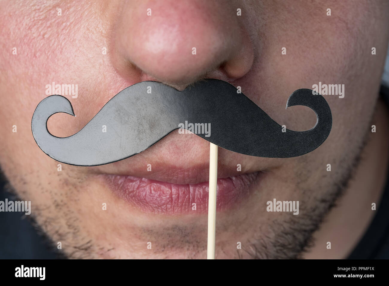 Man with photo booth prop moustache for november cancer awareness month. - Stock Image