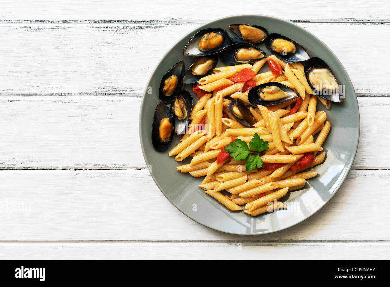 Penne pasta with mussels on a white wooden rustic table. Top view, copy space - Stock Image