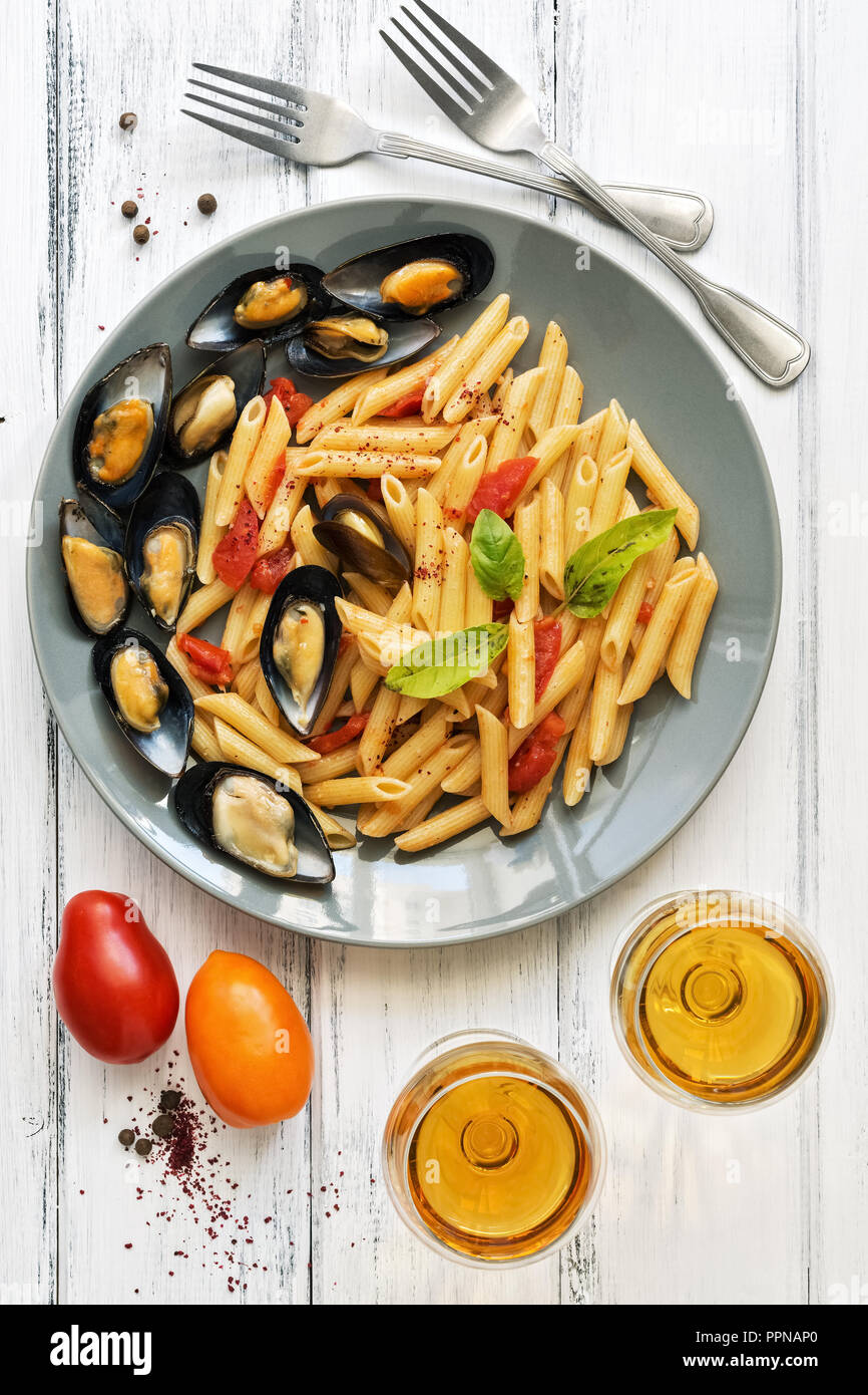 Penne pasta with mussels, tomatoes and white wine on a white wooden rustic background. Top view,flat lay. Mediterranean food - Stock Image