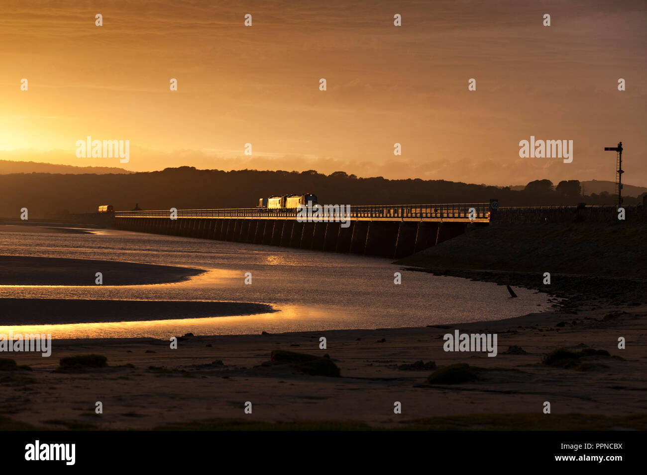 2 Direct rail Services class 88 locomotives crossing Arnside  viaduct over the river Kent at sunset with a nuclear flask catching the golden light - Stock Image