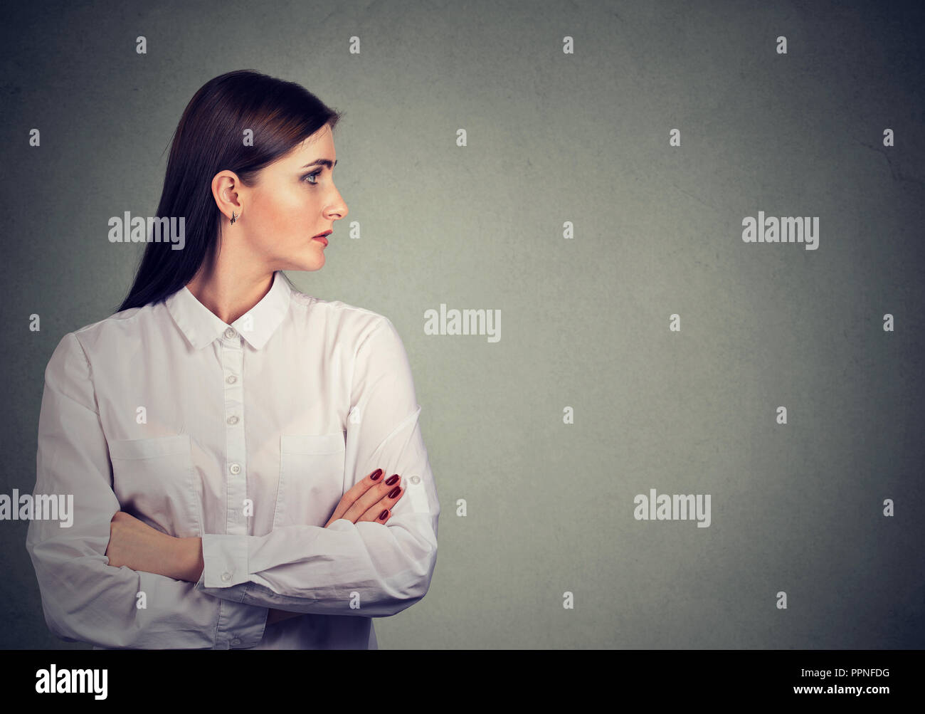 Young brunette in white shirt holding arms crossed and looking away on gray background - Stock Image
