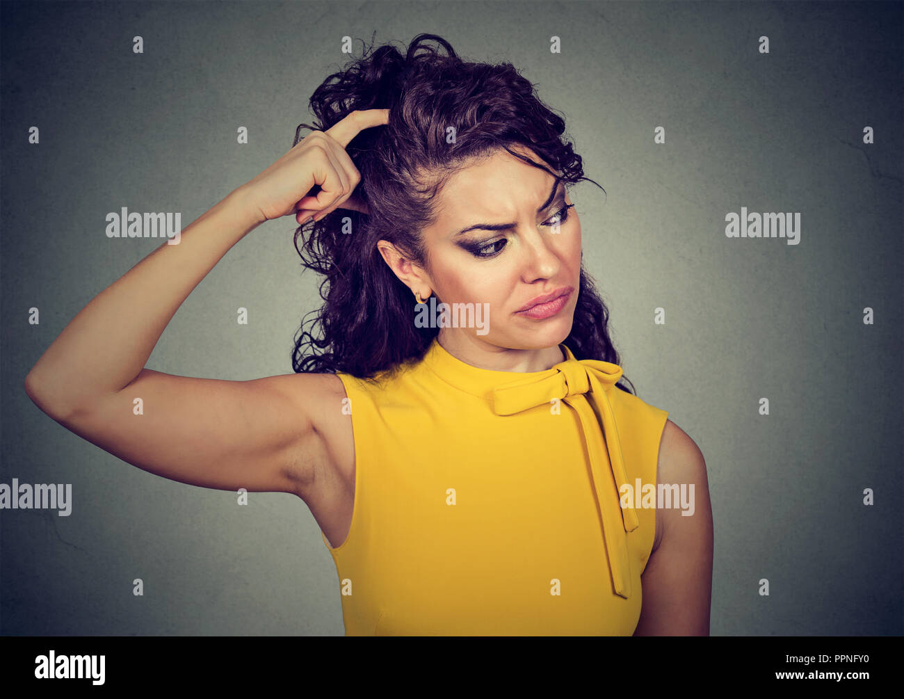 Young puzzled brunette woman in yellow dress scratching head in perplexion looking away - Stock Image
