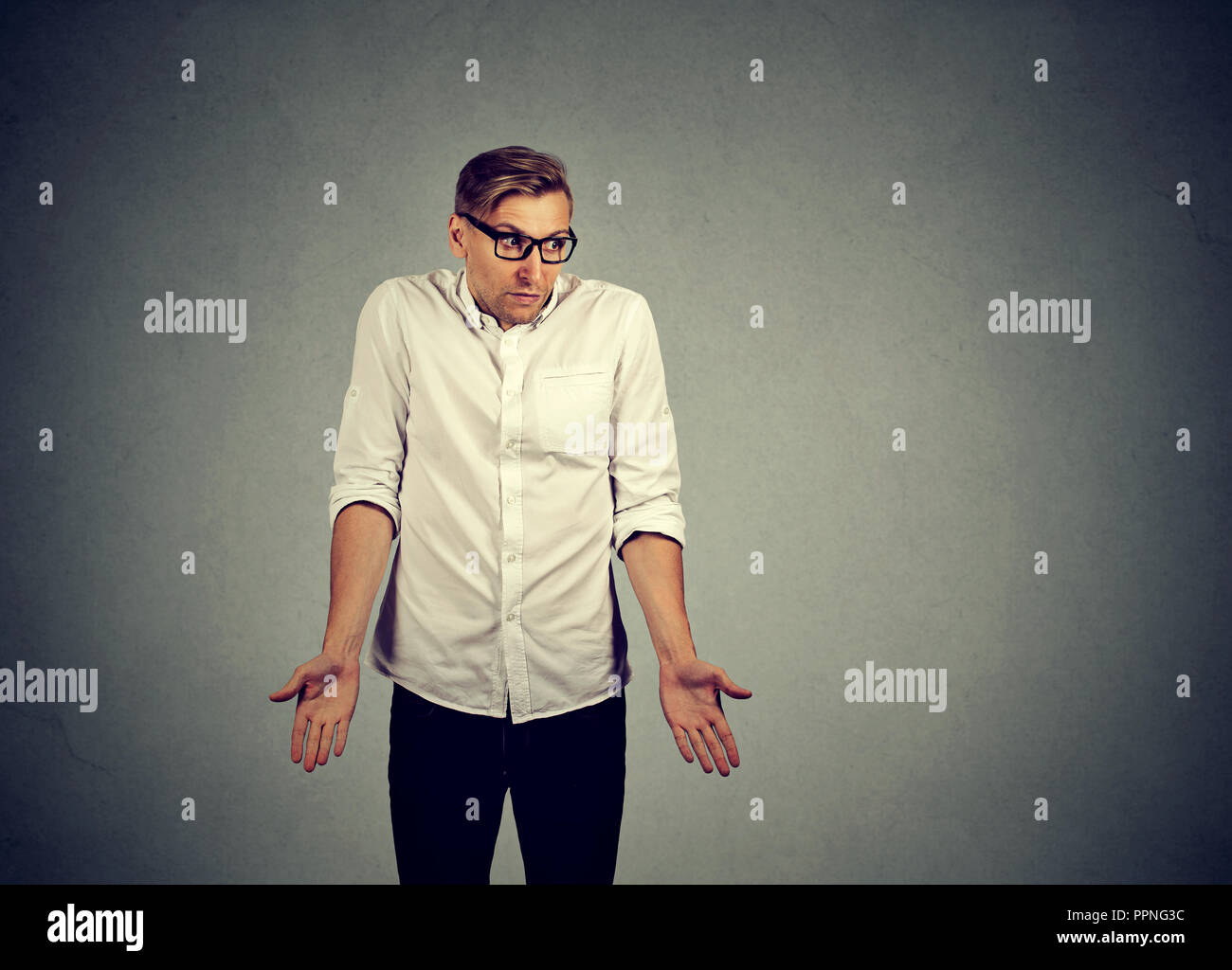 Adult man in glasses and white shirt shrugging shoulders in ignorance looking clueless on gray background - Stock Image