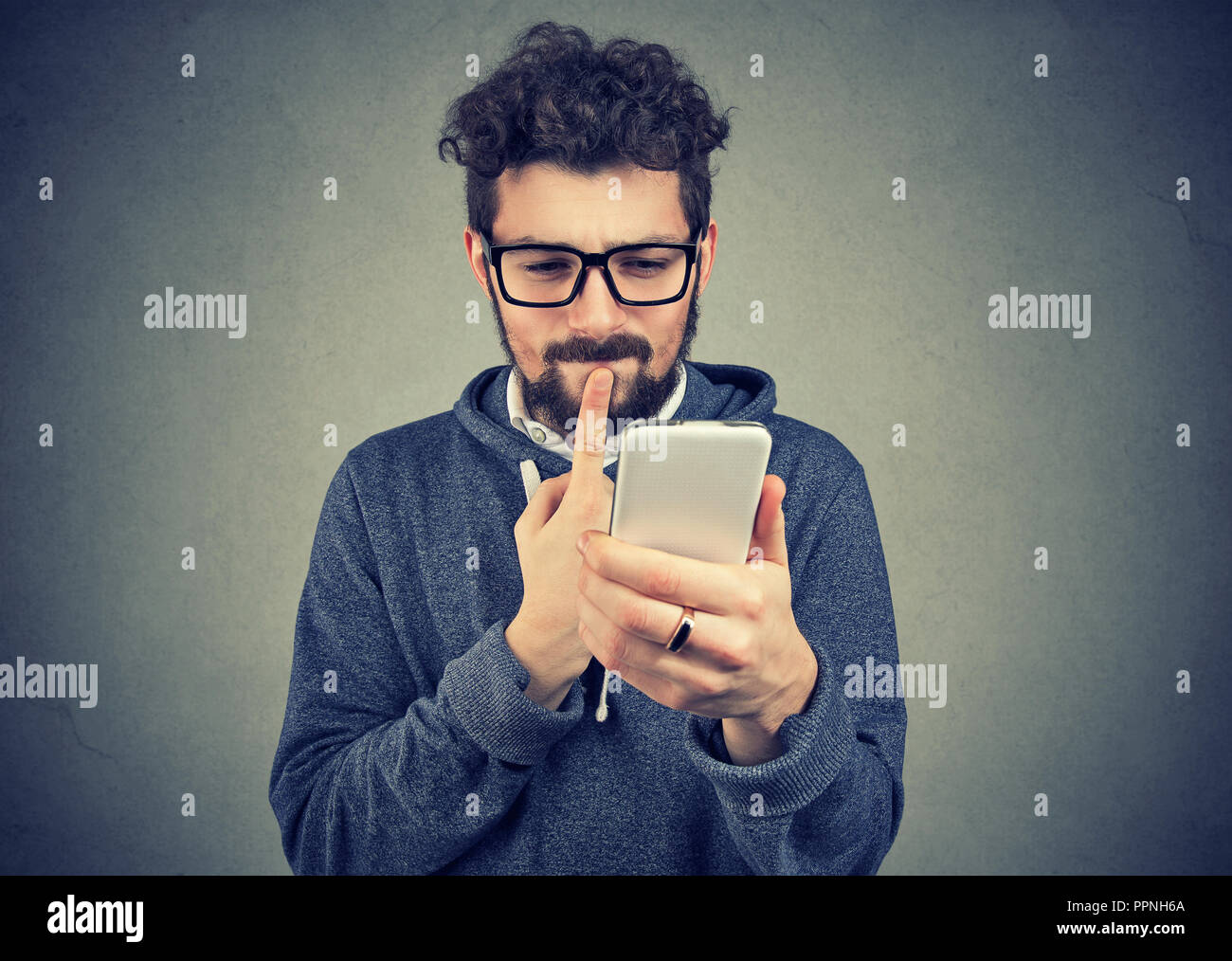 puzzled man thinking what to reply to received text message on cell phone isolated  on gray wall background. Face expression reaction body language - Stock Image