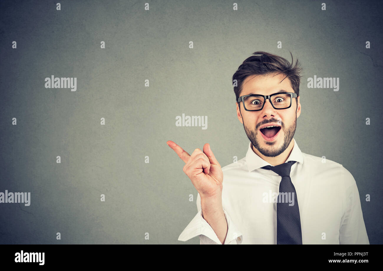 Handsome young man in glasses and formal shirt pointing away showing new offer and smiling at camera - Stock Image