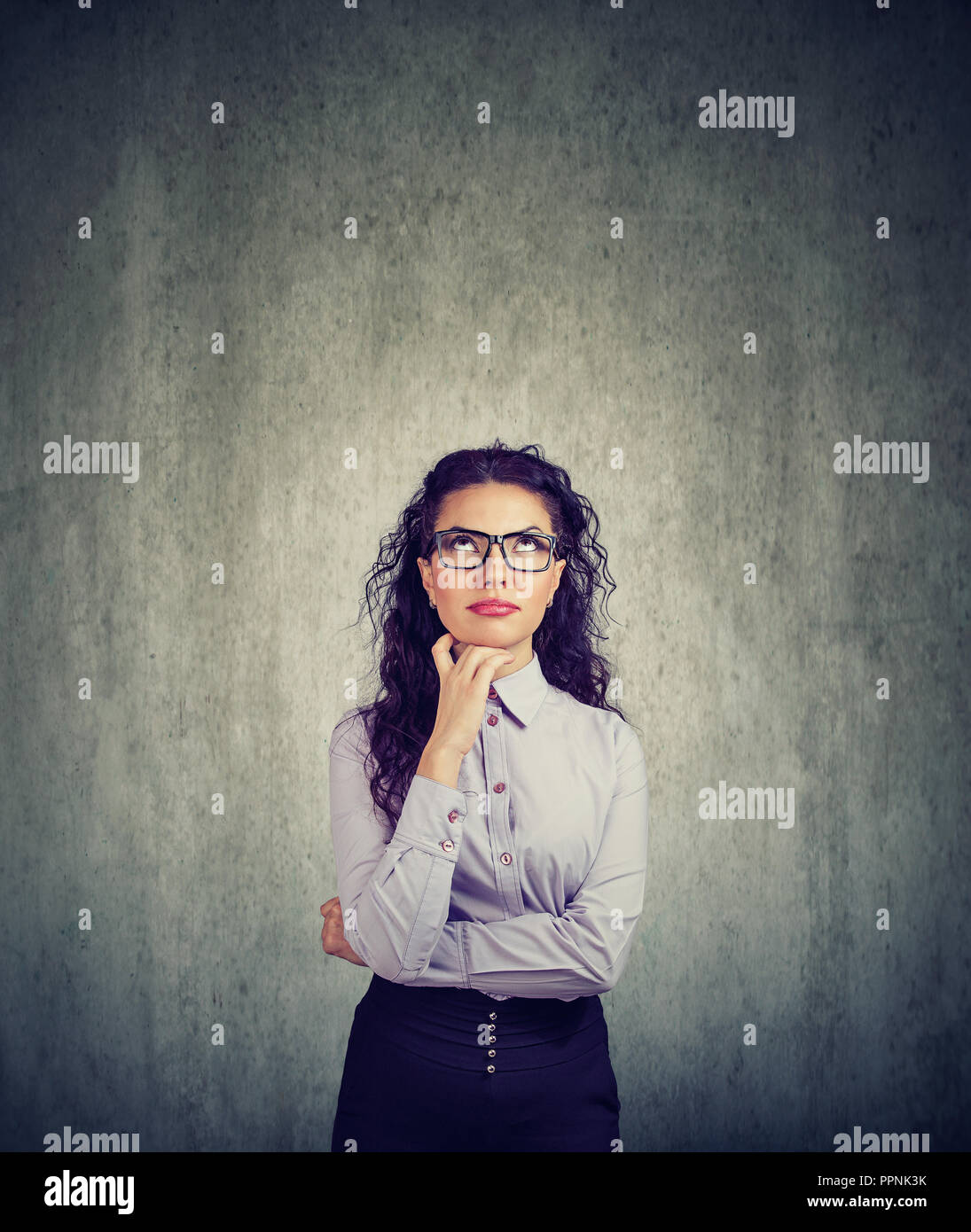 Young brunette woman in eyeglasses looking up in contemplation on gray background - Stock Image