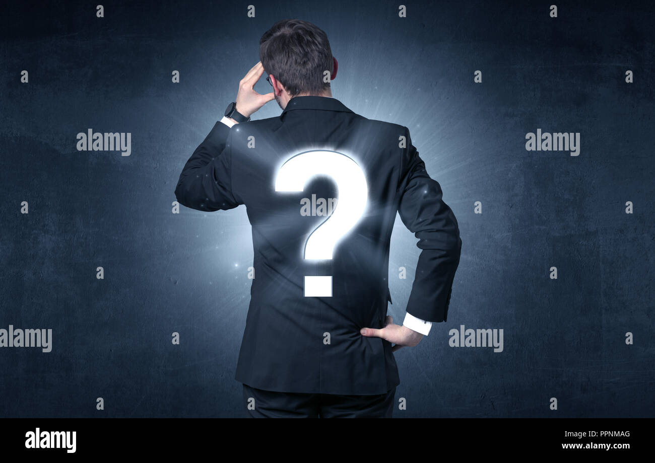 Businessman standing and thinking about questions - Stock Image
