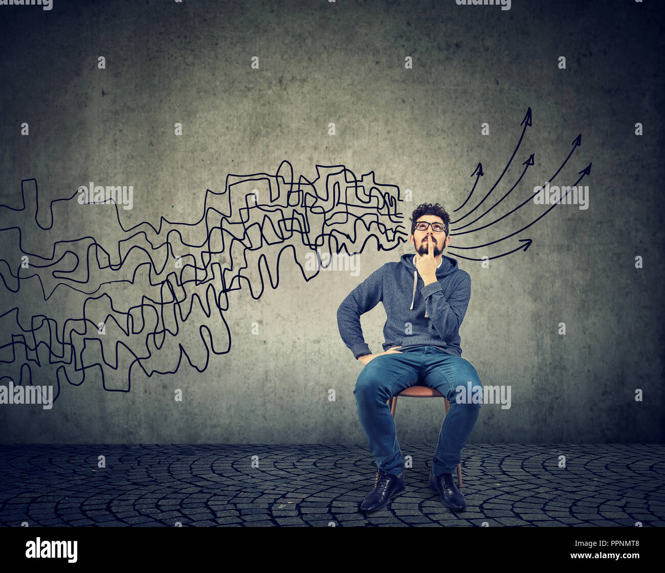 man looking up brainstorming getting his thoughts together planning making conclusions isolated on gray wall background - Stock Image