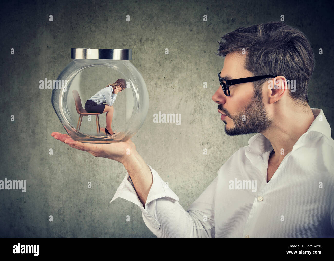 Businessman holding a glass jar with a young sad businesswoman trapped in it - Stock Image
